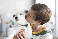 Woman kissing her dog - RBF05701