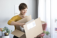 Smiling woman unpacking parcel at home - RBF05716