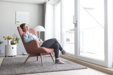 Woman relaxing on armchair at home - RBF05725