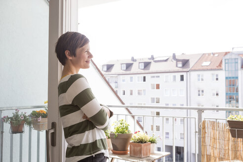 Smiling woman standing on balcony looking at distance - RBF05728
