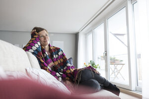 Smiling woman relaxing on the couch - RBF05731