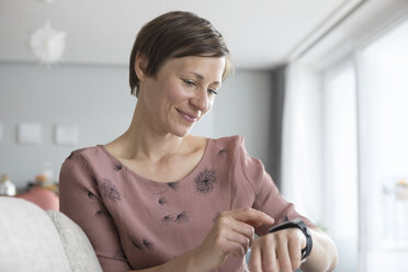 Portrait of smiling woman using smartwatch at home - RBF05737