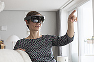 Woman at home using Augmented Reality Glasses at home - RBF05740