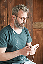 Bearded man looking at smartphone - RTBF00895
