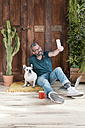 Bearded man sitting with his dog on the floor at home taking selfie with smartphone - RTBF00898