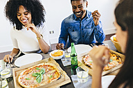 Group of friends having a pizza at home - GIOF02738