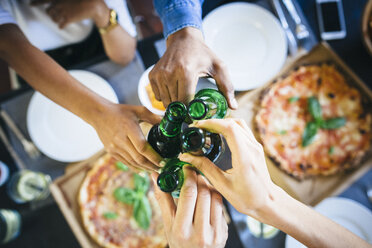 Group of friends having pizza and beer at home - GIOF02741