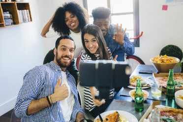 Group of friends posing for a selfie at dining table at home - GIOF02756