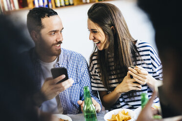 Happy couple sharing cell phone at dining table - GIOF02765