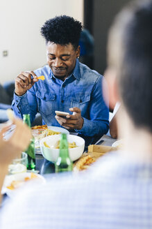 Smiling man looking at cell phone at dining table - GIOF02768
