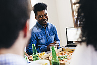 Young man at dining table sharing laptop with friends - GIOF02774