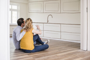 Young couple in new home sitting on floor thinking about interior design - UUF10811