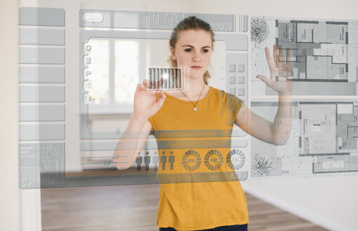 Young woman organizing virtual house model - UUF10814