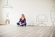 Young woman in new home sitting on floor thinking about interior design - UUF10817
