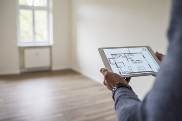 Man in new home holding tablet with floor plan - UUF10820