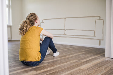 Young woman in new home sitting on floor thinking about interior design - UUF10823