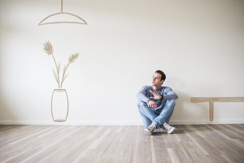 Young man in new home sitting on floor thinking about interior decoration - UUF10826