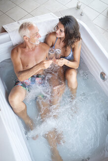 Mature man with younger woman enjoying champagne drinks in jacuzzi hot tub - ABAF02157