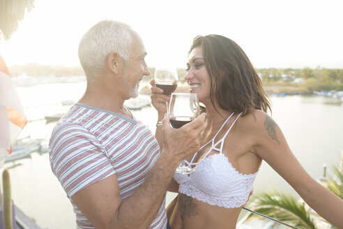 Old man and young woman enjoying red wine on a balcony around sunset - ABAF02160