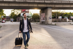 Young man on the move with skateboard, rolling suitcase and headphones - UUF10837