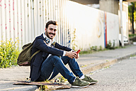 Smiling young man sitting on pavement holding cell phone - UUF10843