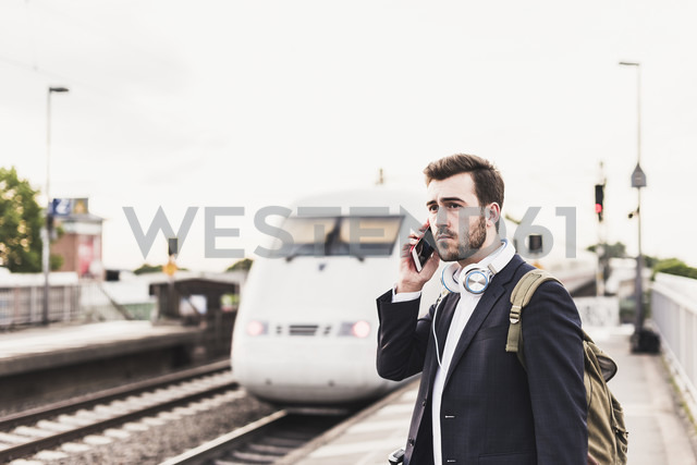 Young man using cell phone on platform as train coming in - UUF10852 - Uwe Umstätter/Westend61
