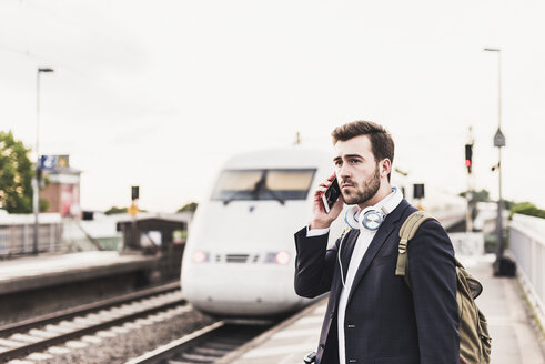 Young man using cell phone on platform as train coming in - UUF10852