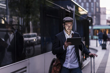 Young man at the bus stop in the city with earphones and tablet - UUF10858