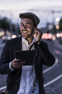 Happy young man in the city with earphones and tablet at dusk - UUF10861