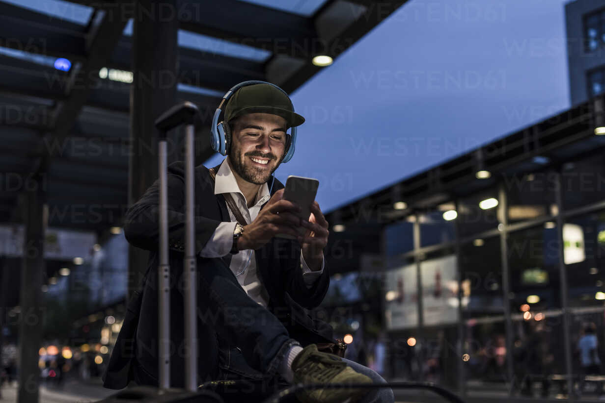 Young man in the city with headphones and cell phone in the evening - UUF10864 - Uwe Umstätter/Westend61