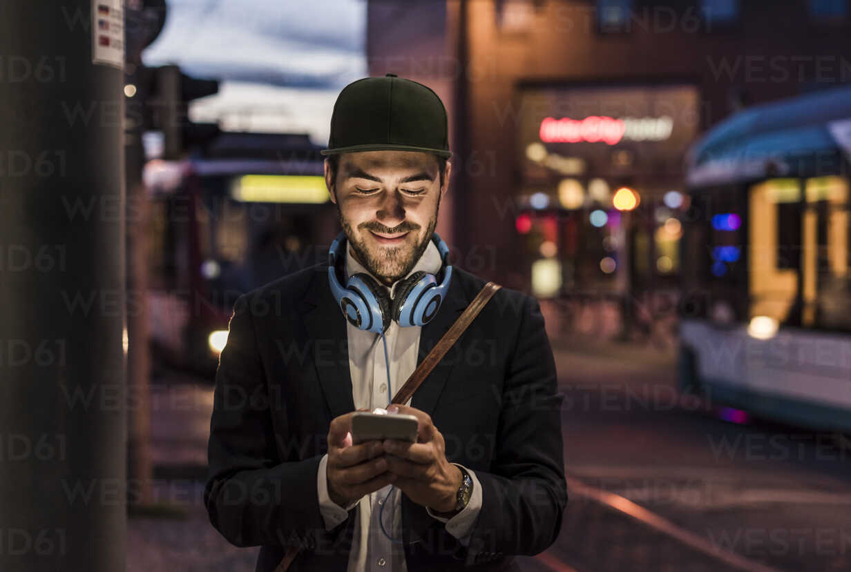 Young man in the city checking cell phone in the evening - UUF10867 - Uwe Umstätter/Westend61