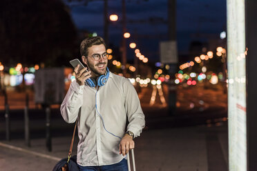 Young man in the city with headphones and cell phone at night - UUF10870