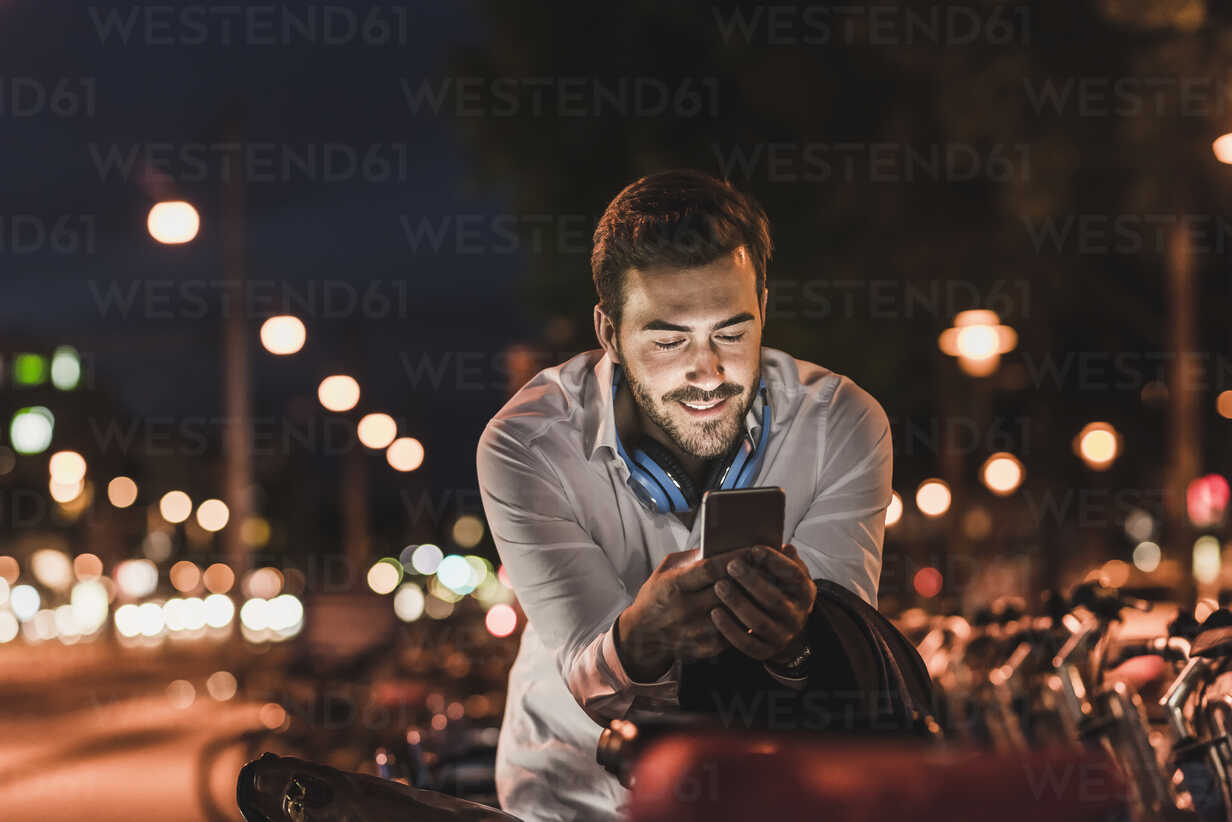 Young man in the city checking cell phone at night - UUF10873 - Uwe Umstätter/Westend61