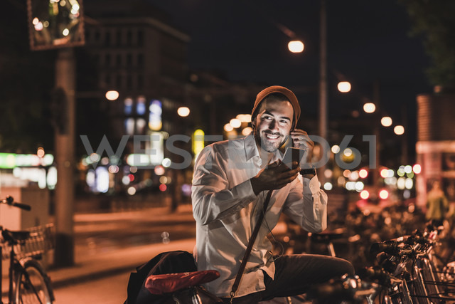 Young man in the city with eardphones and cell phone at night - UUF10876 - Uwe Umstätter/Westend61
