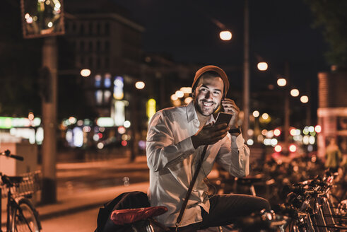 Young man in the city with eardphones and cell phone at night - UUF10876