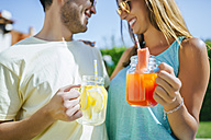 Couple holding refreshing drinks outdoors - KIJF01513