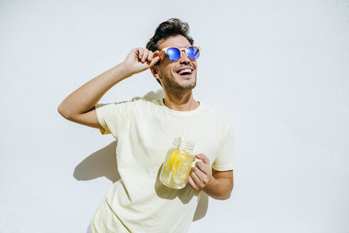 Young an with sunglasses and lemonade in front white wall - KIJF01516