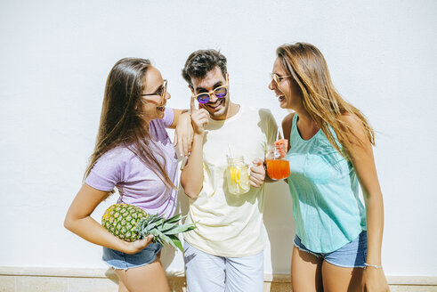 Happy friends holding refreshing drinks  and pineapple in front of white wall - KIJF01519