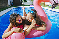 Two young women with pink flamingo float in swimming pool - KIJF01528