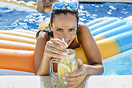Young woman in swimming pool with drink at the poolside - KIJF01531