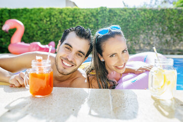 Happy couple in swimming pool with drinks at the poolside - KIJF01534