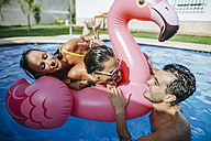 Friends playing in pool with a flamingo float - KIJF01537