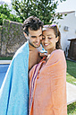 Couple with towels hugging at the poolside - KIJF01540