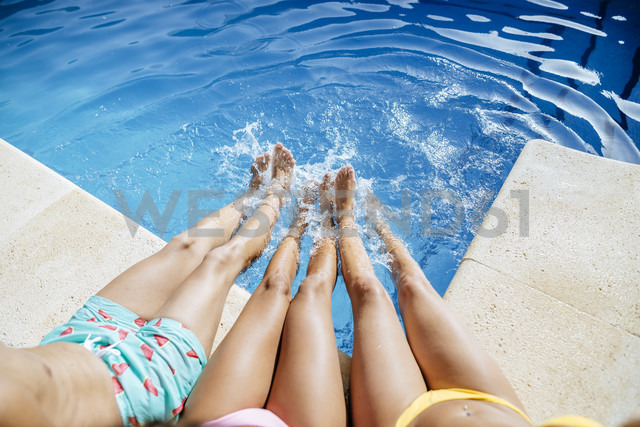 Legs of friends splashing in pool - KIJF01543 - Kiko Jimenez/Westend61