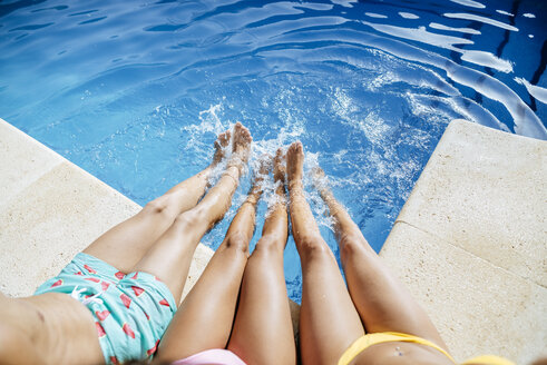 Legs of friends splashing in pool - KIJF01543
