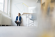 Business woman crouching on floor, looking out of window, thinking - JOSF01134