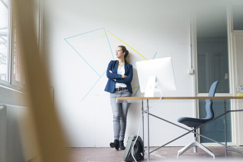 Businesswoman standing in office with arms crossed - JOSF01152