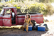 Young woman sitting next to old rusty pick up truck drinking from bottle - ZEF13892