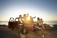 Happy young people outside pick up truck at the coast at sunset - ZEF13916