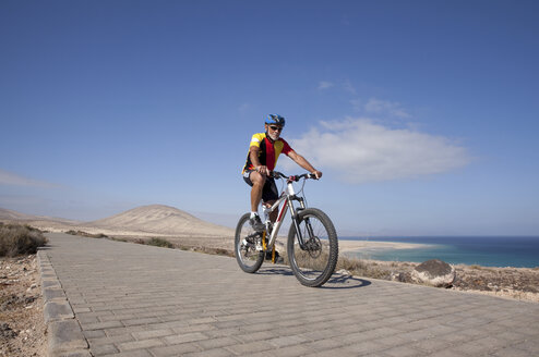 Spain, Canary Islands, Fuerteventura, senior man on mountainbike - MFRF00843